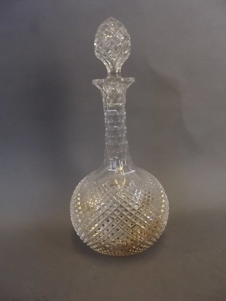 A lead crystal decanter with a cross-cut body, facet