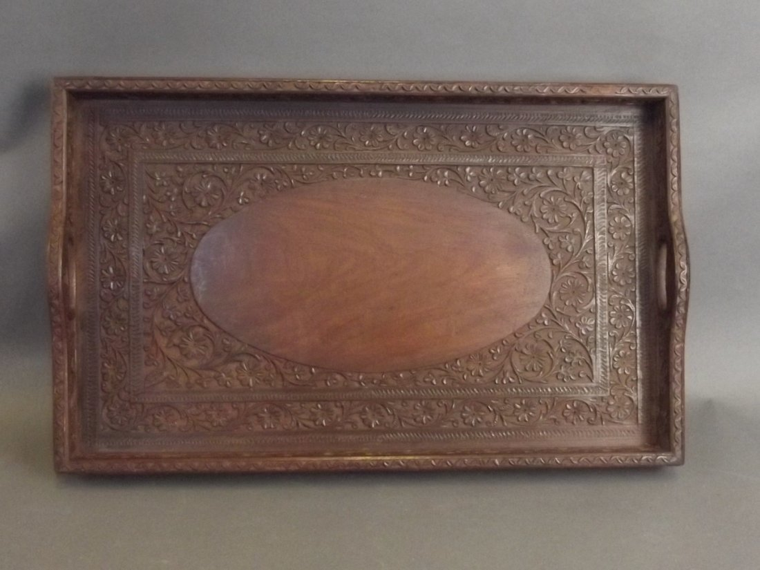 An Indian carved hardwood tray with scrolling floral
