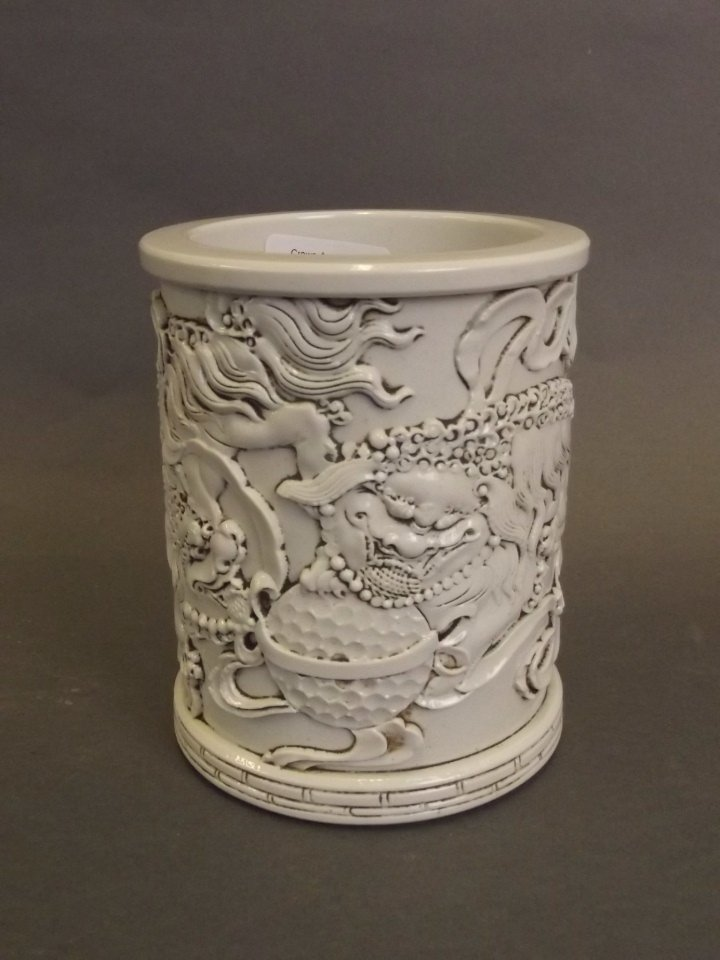 A Chinese Blanc de Chine brush pot with relief twin