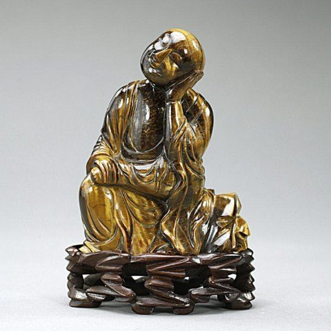 CHINESE CARVED TIGER'S EYE FIGURE OF A SEATED MONK