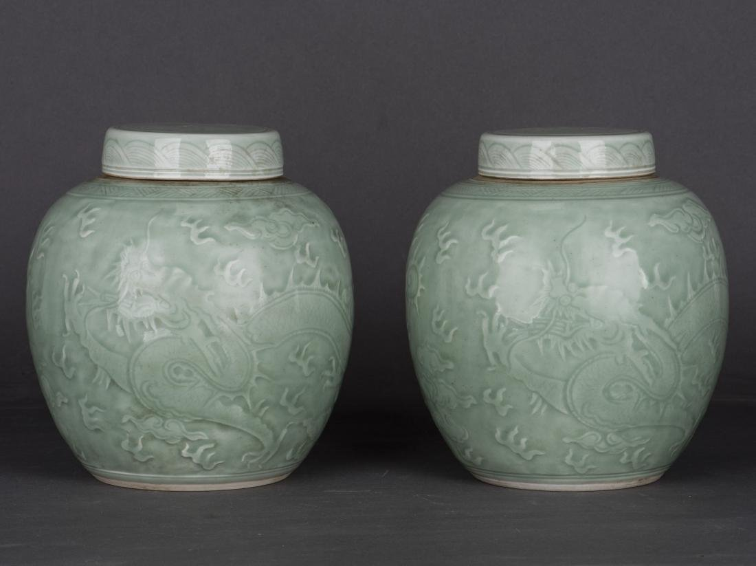 A PAIR OF CELADON-GLAZED 'DRAGON' JAR AND COVERS