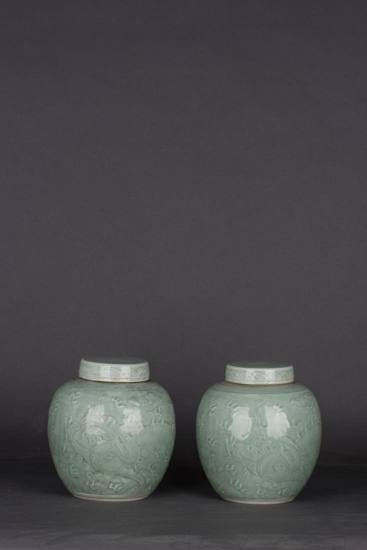 A PAIR OF CELADON-GLAZED 'DRAGON' JAR AND COVERS - 2
