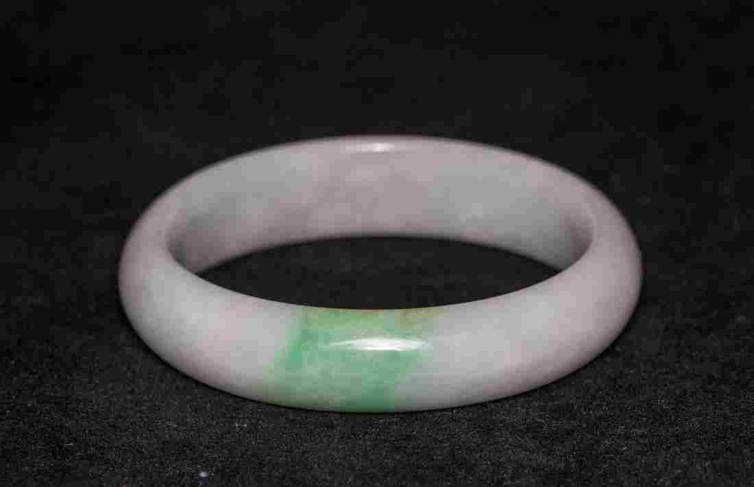 A TRANSLUCENT NATURAL PURPLE AND GREEN JADE BANGLE WITH