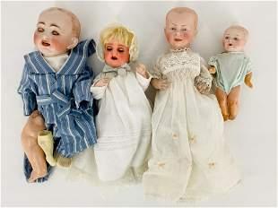 Lot of (4) bisque socket head baby dolls. Boy doll leg