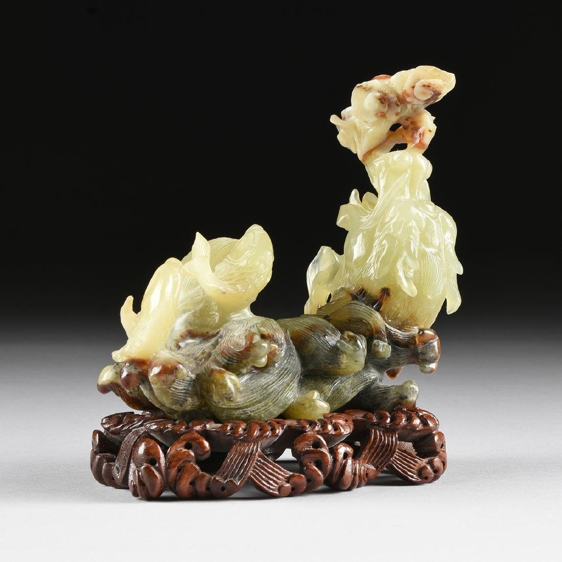 A CHINESE CELADON JADE SEA DRAGON AND FISH GROUP,