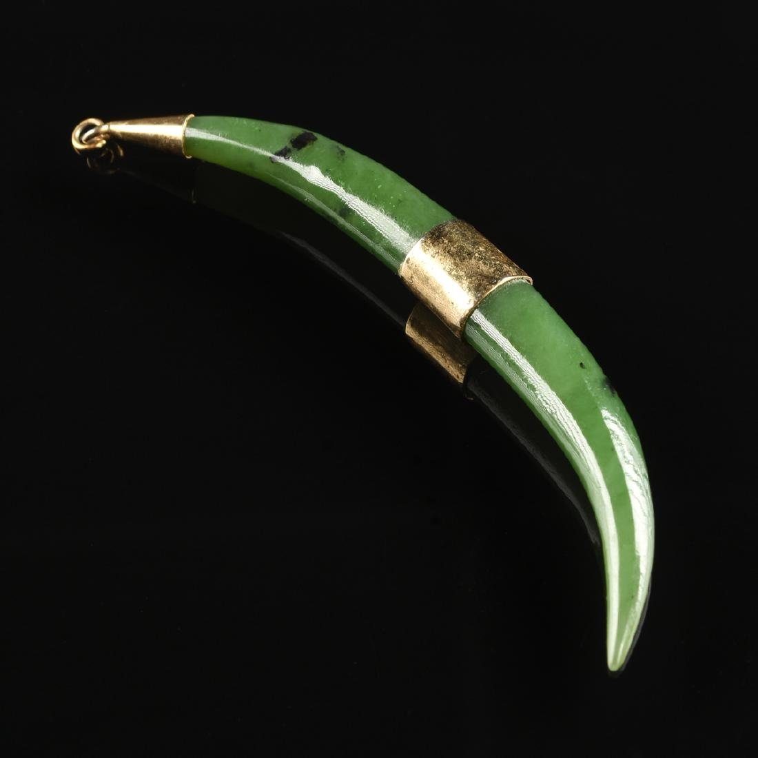 AN EAST ASIAN GREEN JADE DOUBLE TUSK PENDANT,