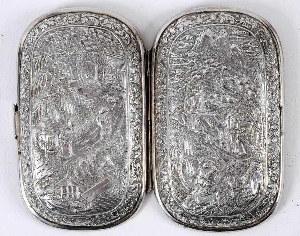 A Chinese silver coloured metal sewing case, embossed