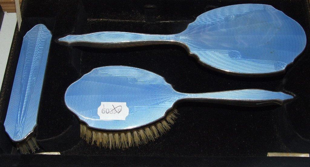 A three piece enamel brush set, cased