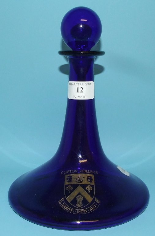 A blue glass decanter and stopper, with Clifton College