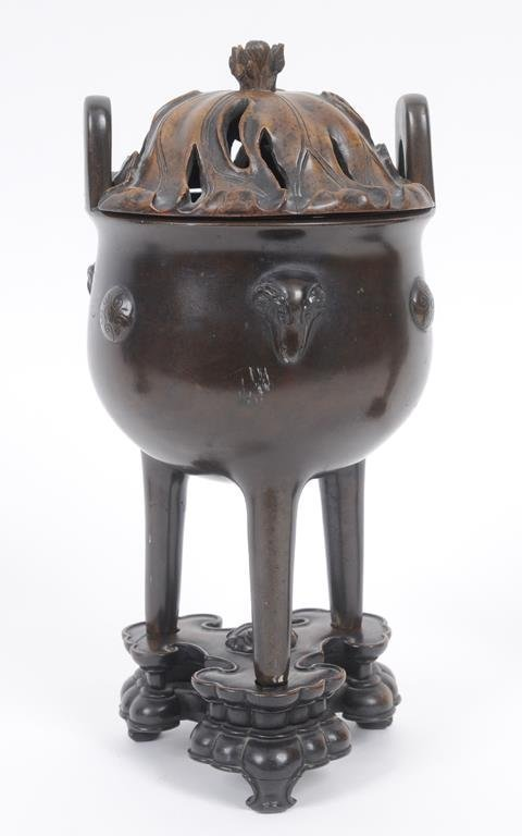 A Chinese bronze censer, decorated roundels and ram's