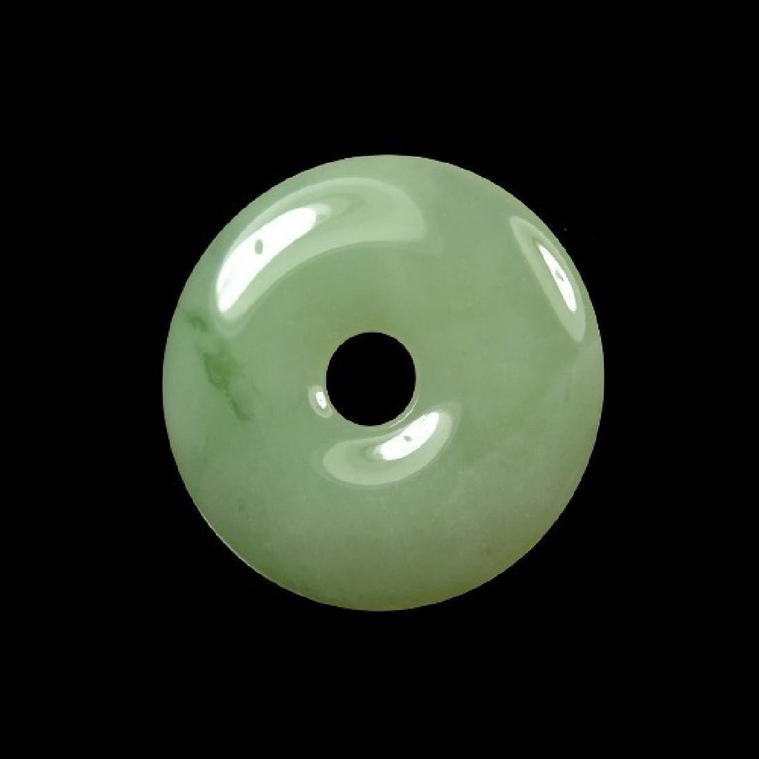 A GREEN JADEITE CARVED RING PENDANT