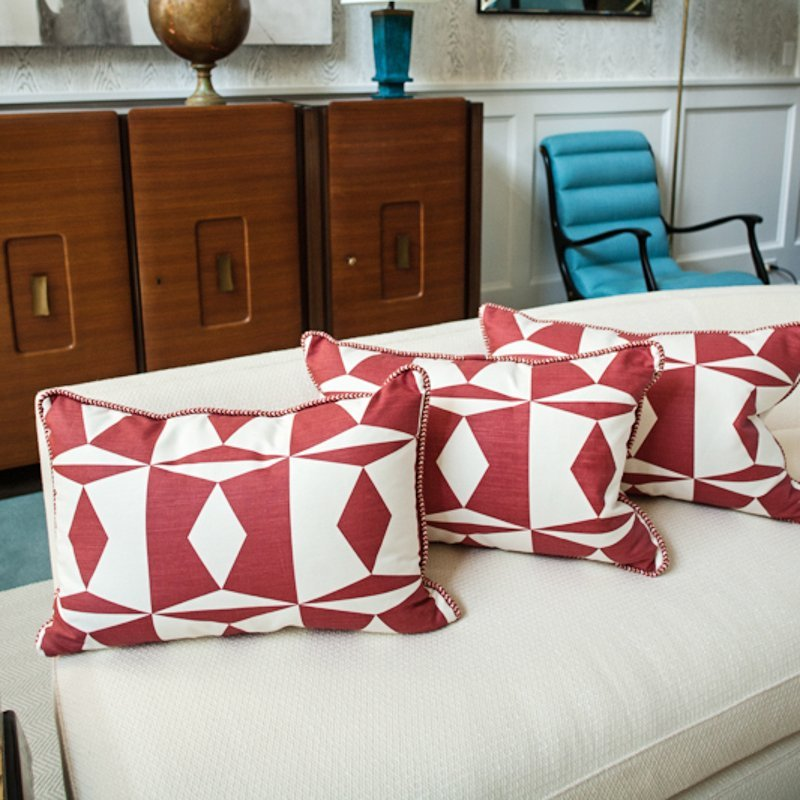 "Three 16"" x 24"" pillows of red and white geometric"