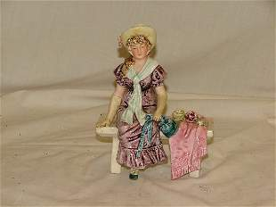 "6.5"" Majolica figurine of girl sitting on"