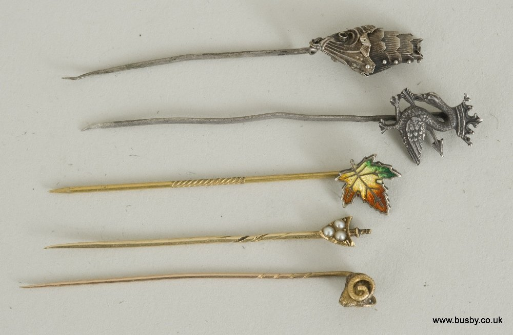A collection of five gold and silver tiepins
