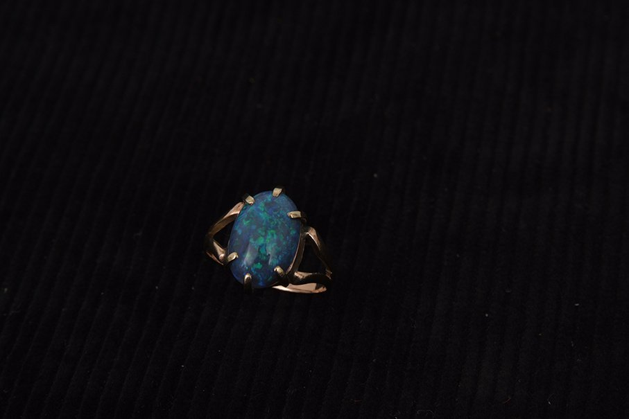 A gold single stone black opal ring, unmarked, size N.
