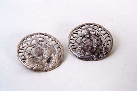 A pair of Art Nouveau silver buttons, pierced with the
