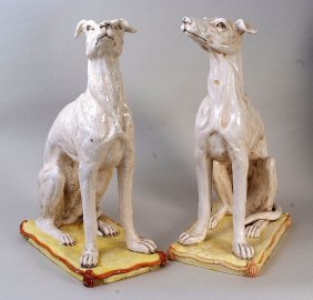 A pair of continental majolica figures of Greyhounds,