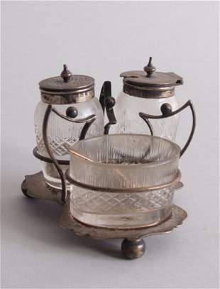 A silver and cut glass three piece condiment set by