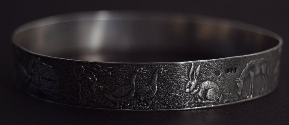 A silver bangle with an engraved scene depicting