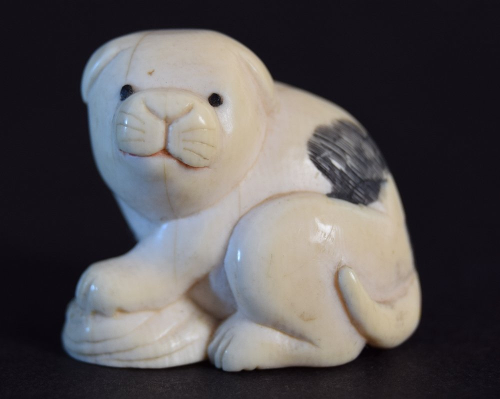 A Japanese netsuke in the form of a crouching puppy,