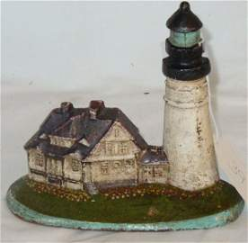 39: antique lighthouse doorstop in old paint