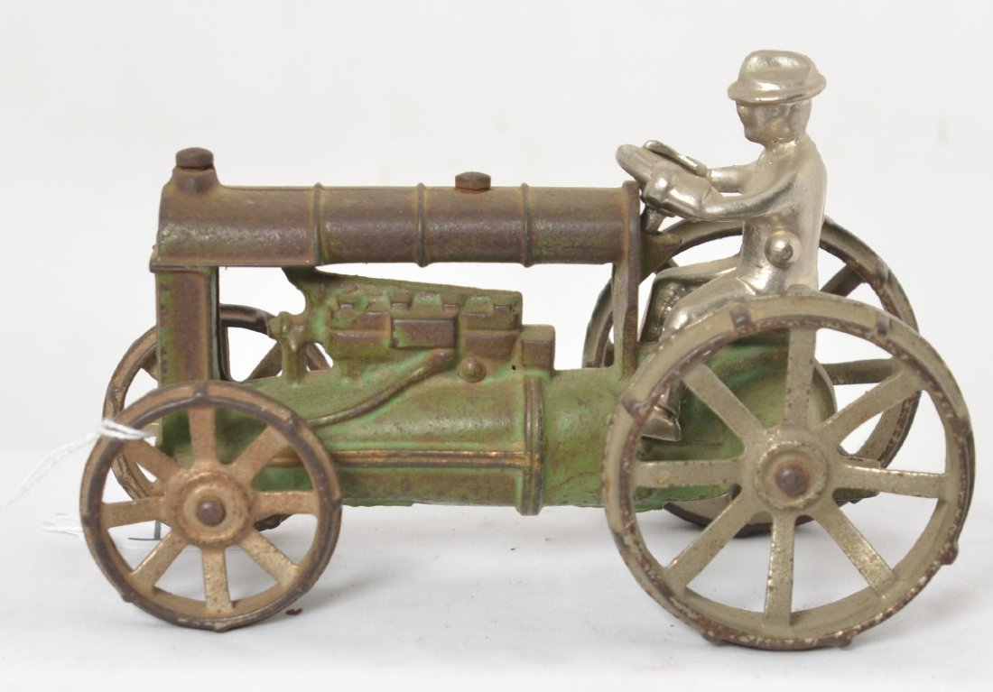 Early cast iron tractor with steel wheels, driver,