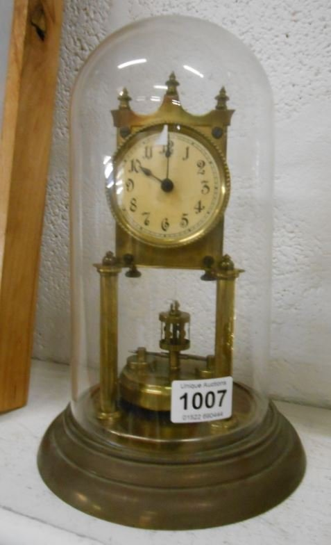 A brass anniversary clock under glass dome