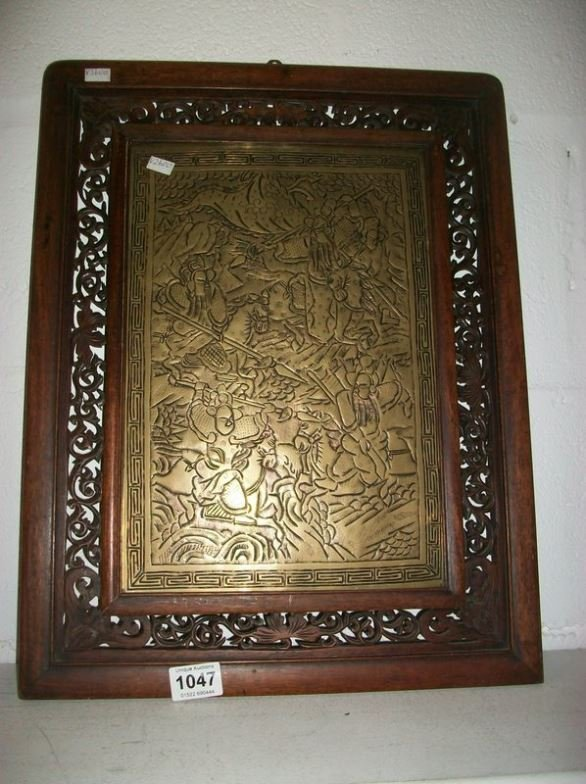 An Oriental brass plaque with ornate wood frame