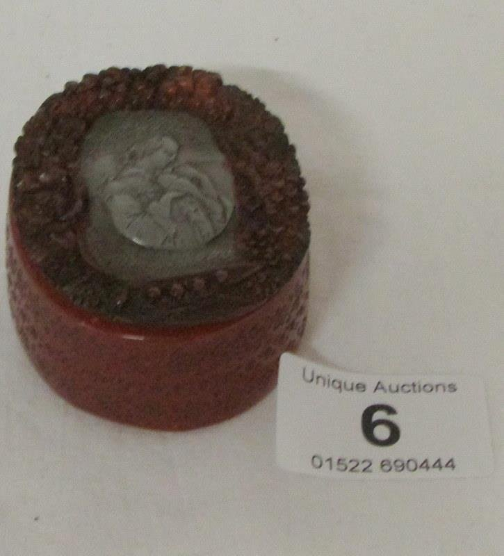 An amber pill box with pewter inset depicting lady with