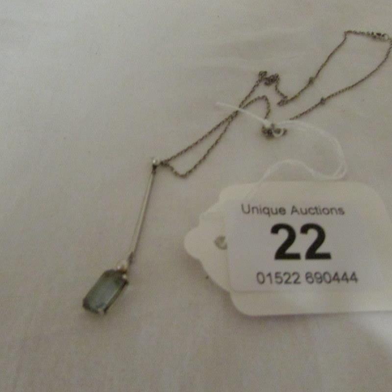 An aquamarine pendant on silver chain