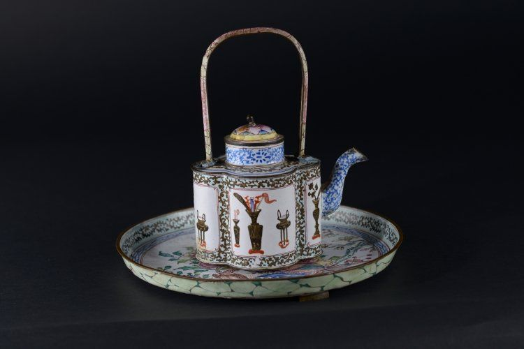 An enamelled teapot and small plate