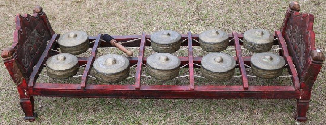 20TH C. TIBETAN GONG ON CARVED AND PAINTED BED