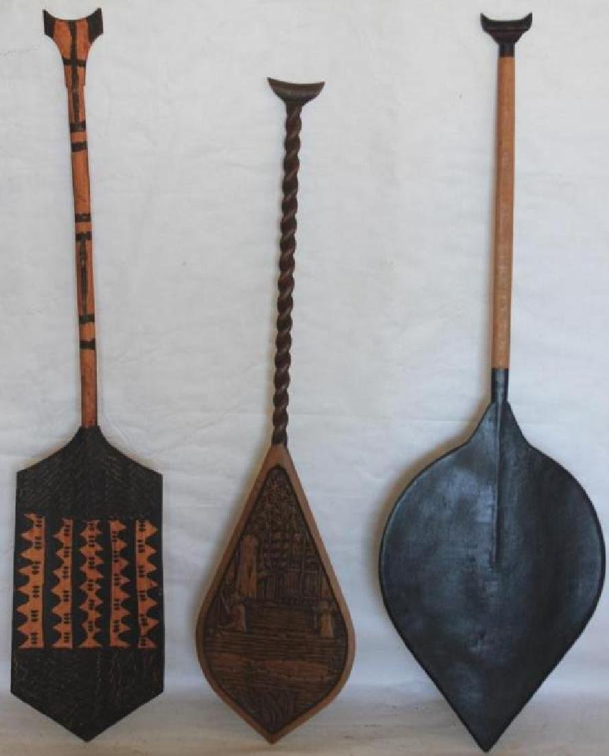 THREE 20TH C. CARVED WOODEN PADDLES FROM THE