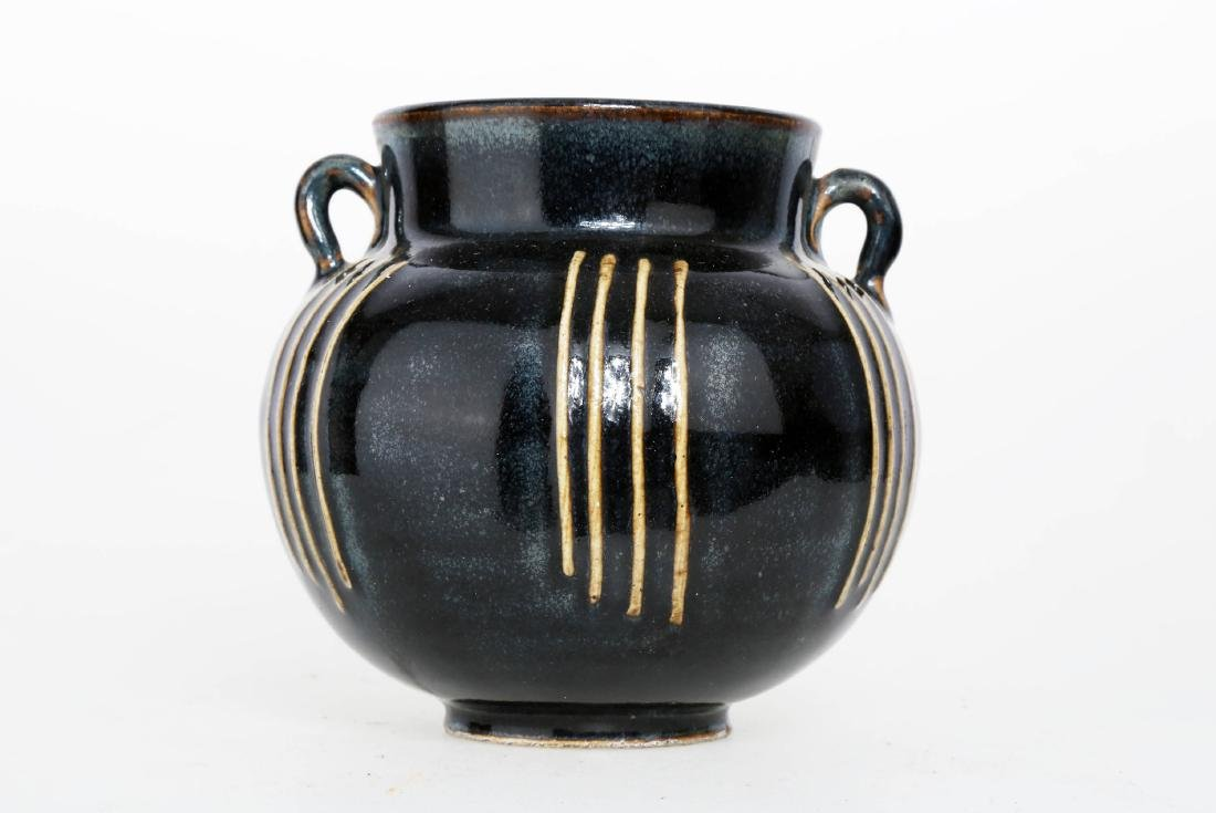 A BLACK GLAZE PORCELAIN HANDLED EWER WITH TWO