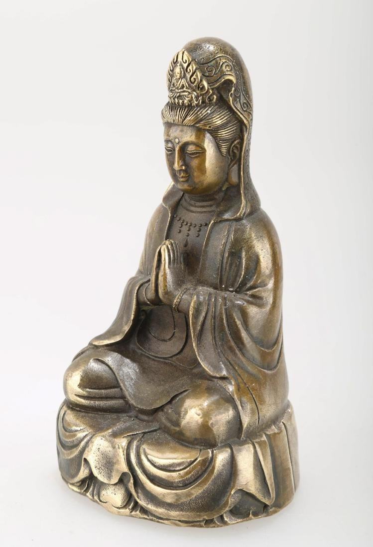 A BRONZE GUANYIN STATUE. THE BASE CARVED WITH MING