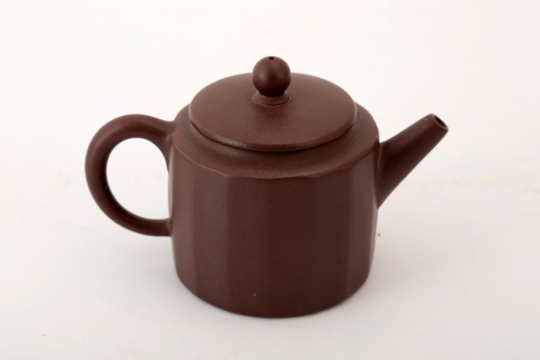 A CLAY TEAPOT WITH MELON RIDGES.
