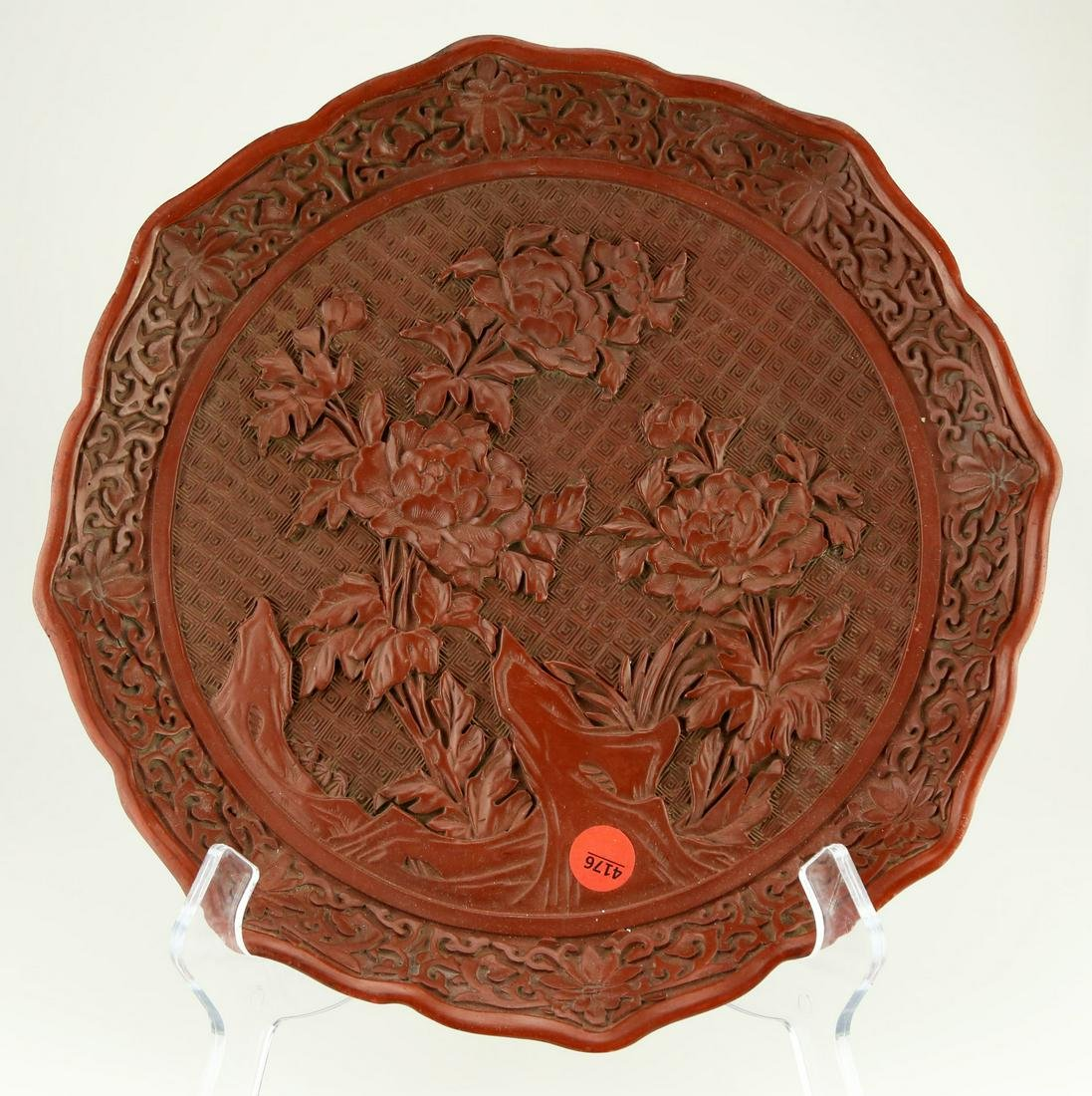 A CINNABAR LACQUER CARVED PLATE. THE BASE MARKED WITH