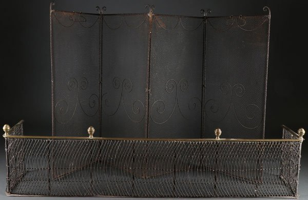 AN EARLY AMERICAN WROUGHT IRON AND BRASS FIRE FENDER