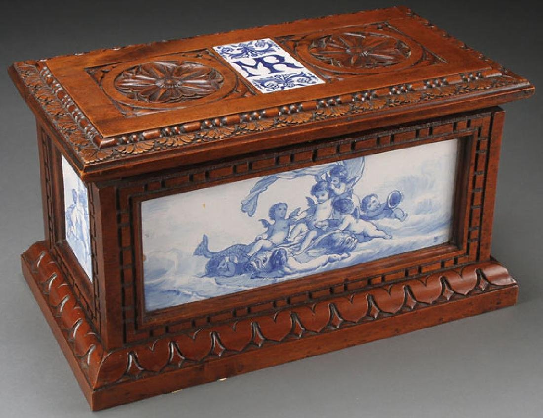 AN ITALIAN CARVED WALNUT AND MAJOLICA CASKET