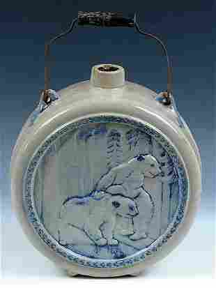 A BLUE GRAY SCENIC BEAR EMBOSSED STONEWARE JUG of