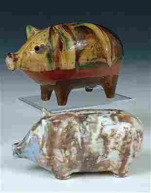 A PAIR OF GLAZED POTTERY PIG BANKS the largest in