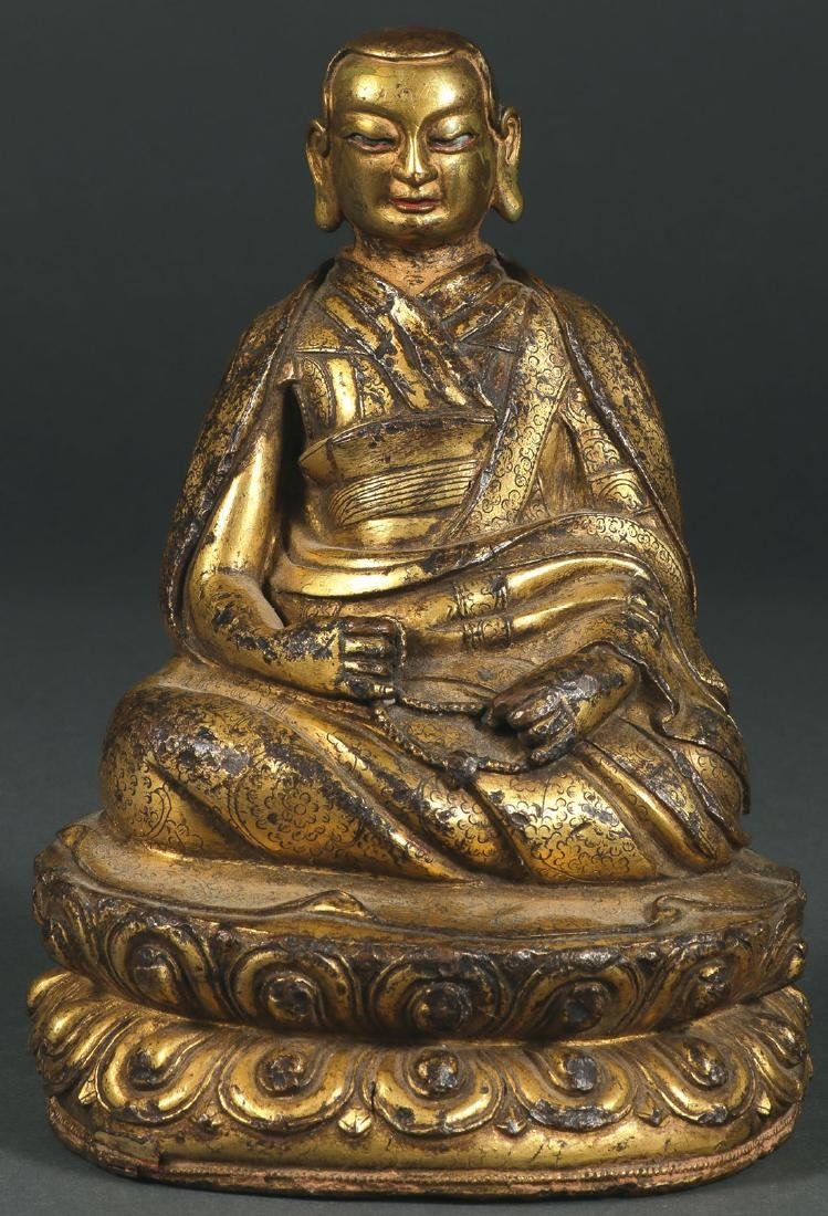 A SINO-TIBETAN GILT COPPER FIGURE OF A MONK