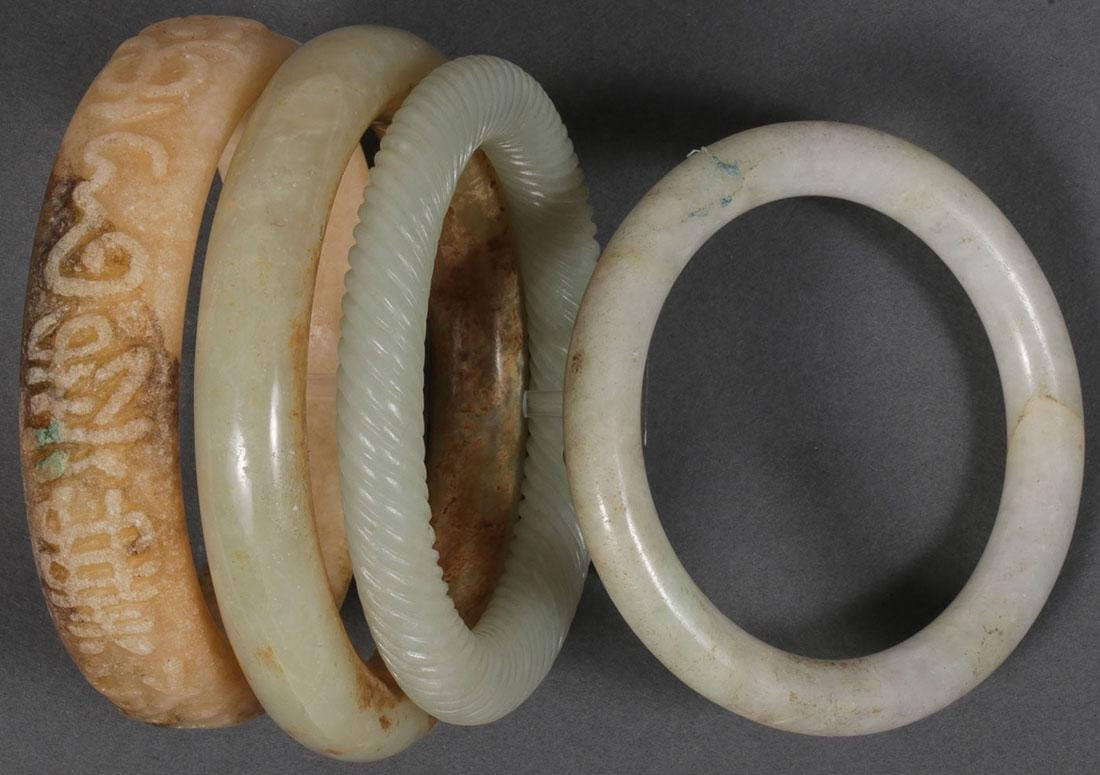 FOUR CHINESE CARVED JADE AND HARDSTONE BRACELETS