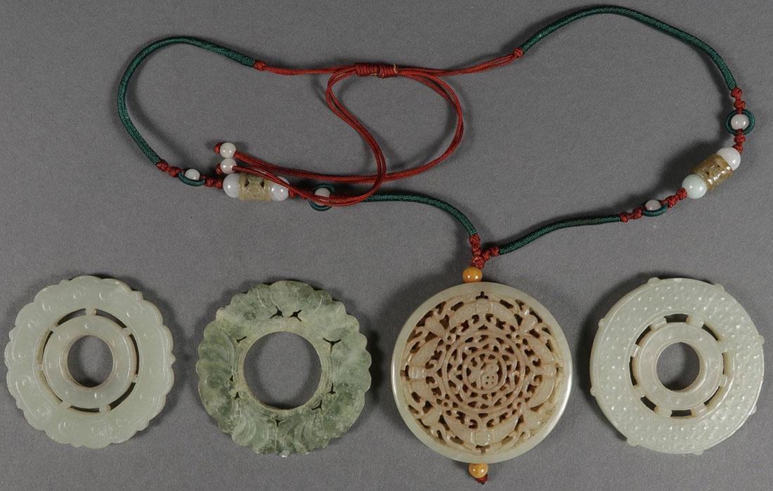 FOUR GOOD CHINESE CARVED JADE DISC FORM PENDANTS