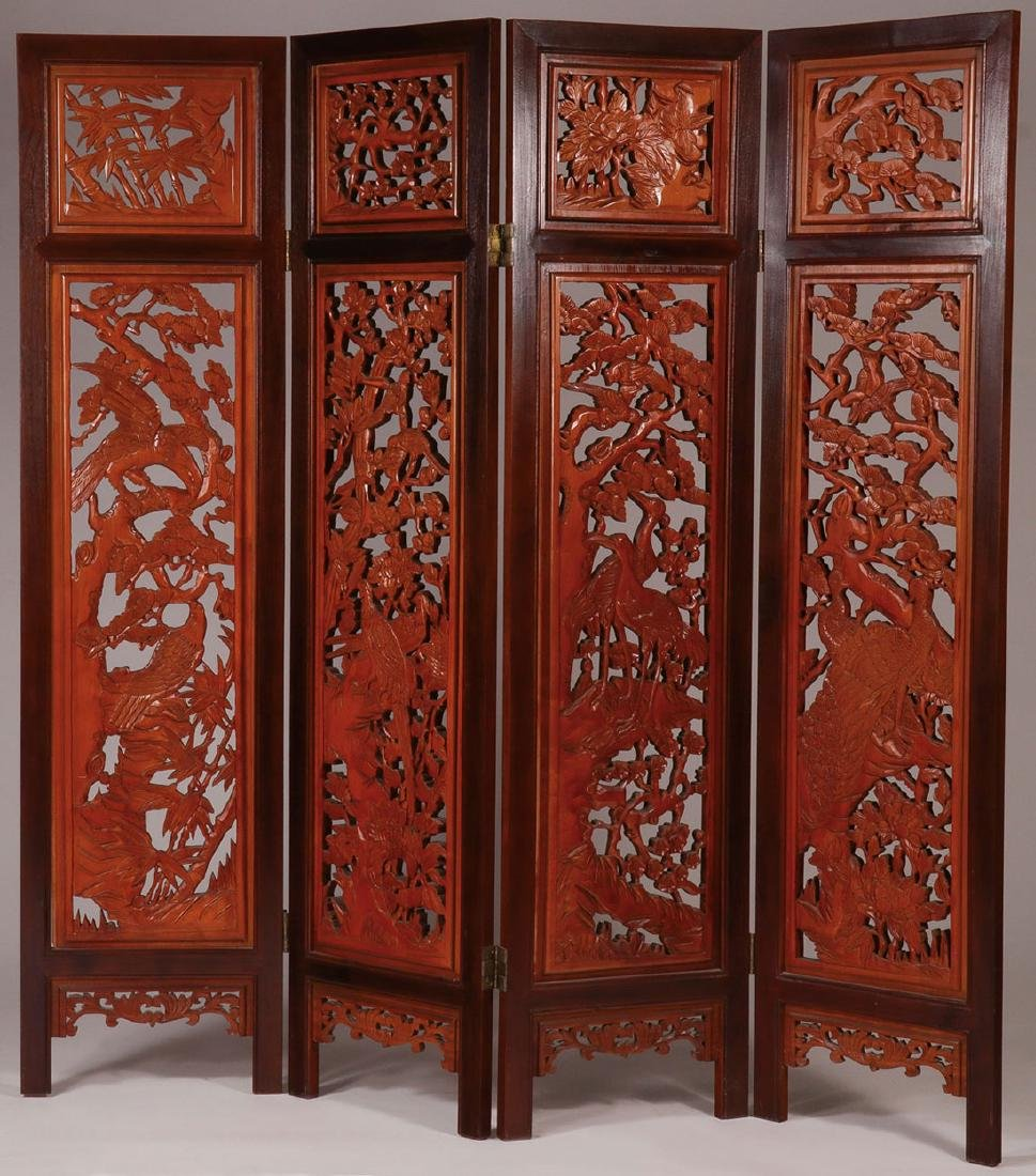A LARGE HEAVILY CARVED CHINESE FOLDING SCREEN