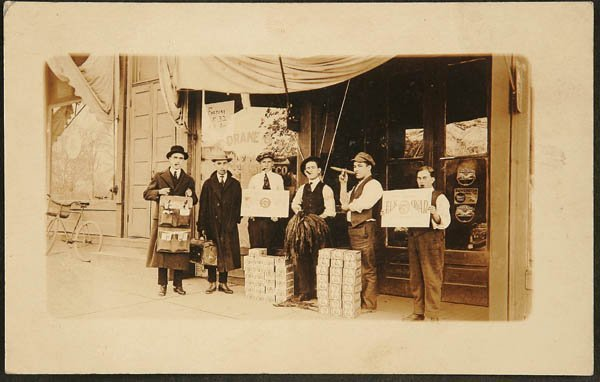 1516:  RPPC of a tobacco store front Elk Cigars advert.