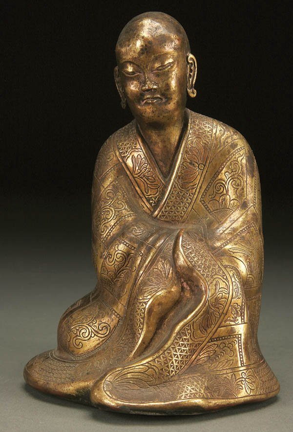771: A CHINESE GILT-COPPER SEATED FIGURE OF A MONK