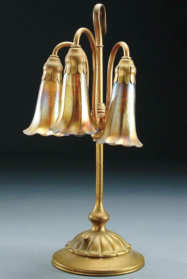 18: A TIFFANY DORE BRONZE/FAVRILE GLASS 3-LILY LAMP