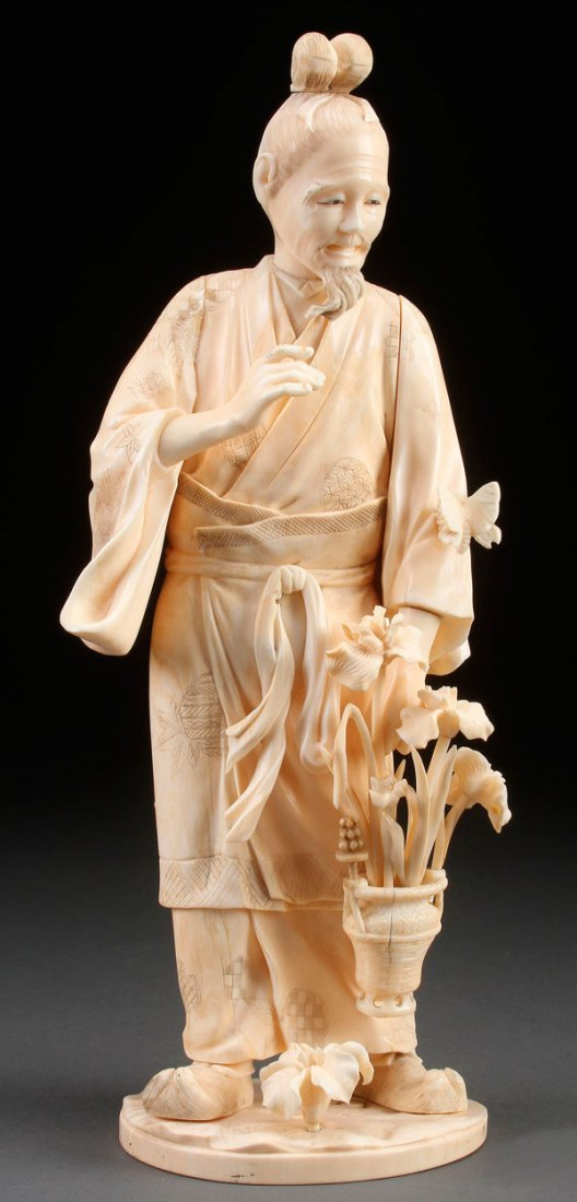 A LARGE JAPANESE CARVED IVORY OKIMONO OF A GARDENER