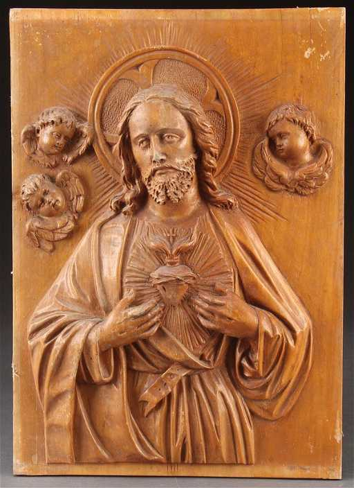 A carved wood relief plaque of the sacred heart